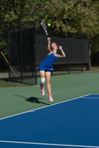 Aly Henneberry reaches for a return at a home tennis match.