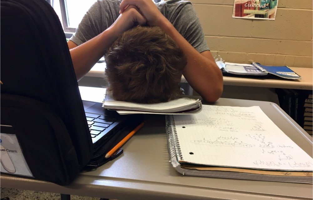 student with head down on books